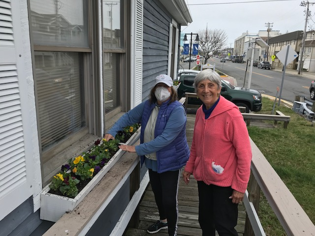 "Lisa, here is an ""historic"" picture during this time. Garden club president, Sandy Slabik, in mask, and Peg Sutton(chair basket, urns and plant sale), planting pansies at the bridge tender's house at 96th St. bridge"